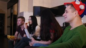 谈论四的年轻人观看足球赛,吃垃圾食品和比赛 股票录像