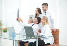 谈论小组的医生X-射线,坐在桌上 免版税图库摄影