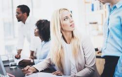 谈论小组四个的工友事务在办公室射出 美丽的妇女谈话与同事 水平,被弄脏的backgro 免版税库存照片