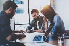 谈论年轻企业的专家新的事务在现代办公室射出 群策群力在的小组三个工友 免版税库存图片