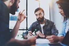 谈论年轻的商人新的事务在现代办公室射出 群策群力在会议上的小组三个工友 免版税图库摄影