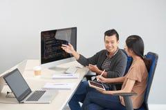 谈论微笑的程序员坐在计算机的工作 免版税库存照片