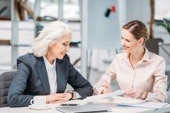 谈论愉快的女实业家事务在会议射出在办公室 免版税库存照片