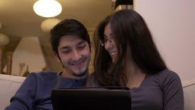 谈论愉快的微笑的和笑的年轻的夫妇观看和在片剂个人计算机的网上喜剧电影 股票视频
