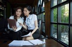 谈论文件和使用一种数字式片剂的可爱的两个亚洲人女实业家 免版税图库摄影