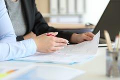 谈论文件的两个办公室工作者 免版税库存照片