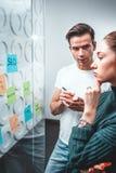 谈论新的想法和使用稠粘的玻璃笔记墙壁的企业同事 免版税图库摄影