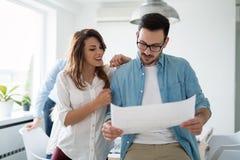 谈论新的想法和群策群力在一个现代办公室的工友 免版税库存照片