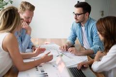 谈论新的想法和群策群力在一个现代办公室的工友 免版税库存图片