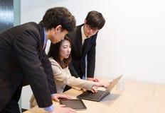 谈论日本企业的人,看互联网网页和文件在个人计算机 库存图片