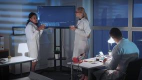 谈论某事的女性工程师在有杯子的电视屏幕附近饮料