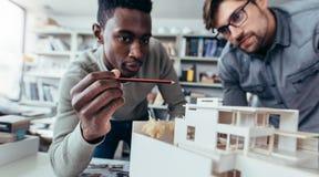 谈论男性的建筑师在办公室工程项目 图库摄影