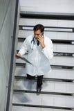 谈论男性的医生在手机的X-射线,当走楼下时 库存照片