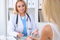谈论的医生和的患者某事,当坐在桌上在医院时 医学和医疗保健概念 库存图片