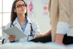 谈论的医生和的患者某事,当坐在桌上时 医学和医疗保健概念 免版税图库摄影