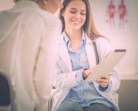谈论的医生和的患者某事,当坐在桌上时 医学和医疗保健概念 免版税库存照片