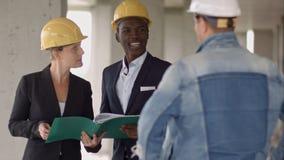 谈论的建造者工作小组看新的项目和它 免版税库存照片
