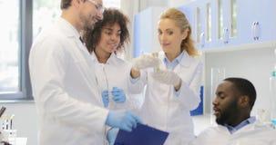 谈论的科学家愉快的队实验Cheerfull,工作在实验室的成功的研究员队的结果 股票视频