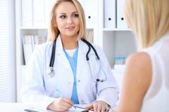 谈论的医生和的患者某事,当坐在桌上时 免版税库存照片