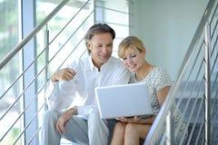 谈论确信的商务伙伴坐在办公楼的台阶和工作,计算机,微笑,成熟商人 库存照片