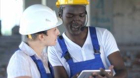 谈论确信的女性的工程师或的建筑师建筑发布与男性同事 库存照片