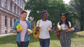 谈论,吃午餐和吃多哥食物的三名年轻不同种族的饥饿的人学生,当站起来室外时 影视素材