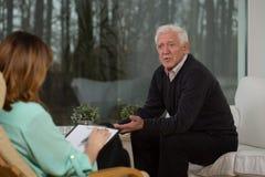 谈论他的问题的退休人员 库存图片