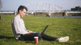 谈话一个的人在公园坐视频通信 学生,自由职业者,微笑并且笑 膝上型计算机人 影视素材