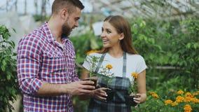 谈话与顾客和提他建议的年轻友好的妇女卖花人,当工作在园艺中心时 免版税库存图片