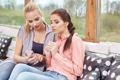 谈话两个妇女的朋友拿着咖啡杯 免版税库存图片