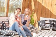 谈话两个妇女的朋友拿着咖啡杯 免版税图库摄影