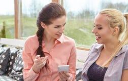 谈话两个妇女的朋友拿着咖啡杯 库存照片