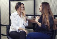 谈话两个的女孩absorbedly,当喝茶在咖啡馆时的柜台 免版税库存照片