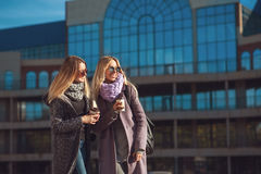 谈话两个美丽的少妇,当走街道时在购物拿着咖啡和微笑以后 天气是伟大的 免版税库存照片