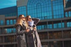 谈话两个美丽的少妇,当走街道时在购物拿着咖啡和微笑以后 天气是巨大tod 免版税库存照片