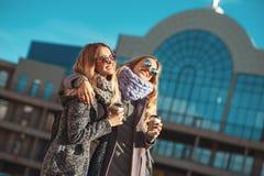谈话两个美丽的少妇,当走街道时在购物拿着咖啡和微笑以后 库存图片