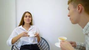 谈话两名女子高中的学生拿着饮料坐一个沙发在客厅 股票视频