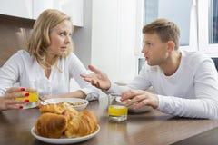 谈话中间成人的夫妇,当食用早餐在家时 免版税库存照片