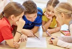 谈话和写在学校的小组学生 免版税库存照片