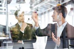 谈话和写在玻璃委员会的两个商人在办公室 免版税库存图片