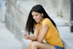 谈话和发短信在巧妙的电话的愉快的年轻拉丁妇女 库存照片