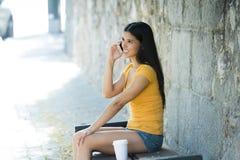 谈话和发短信在巧妙的电话的愉快的年轻拉丁妇女 库存图片