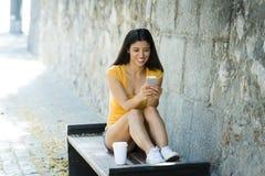 谈话和发短信在巧妙的电话的愉快的年轻拉丁妇女 图库摄影