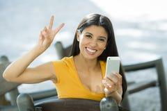 谈话和发短信在巧妙的电话的愉快的年轻拉丁妇女 免版税库存照片
