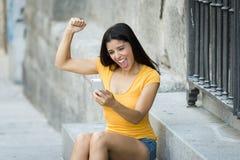 谈话和发短信在巧妙的电话的愉快的年轻拉丁妇女 免版税库存图片