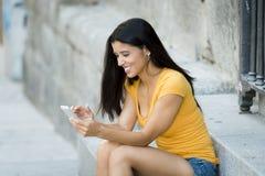 谈话和发短信在巧妙的电话的愉快的年轻拉丁妇女 免版税图库摄影