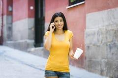 谈话和发短信在巧妙的电话的愉快的年轻拉丁妇女 库存例证