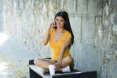 谈话和发短信在巧妙的电话的愉快的年轻拉丁妇女 皇族释放例证