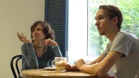 谈话和吃在咖啡馆的年轻有吸引力的millenial夫妇 影视素材