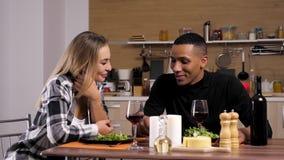 谈话和微笑在厨房里的人种间夫妇 影视素材